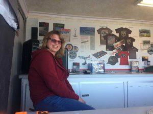 Paula working Randy's shift in the merchandise trailer.